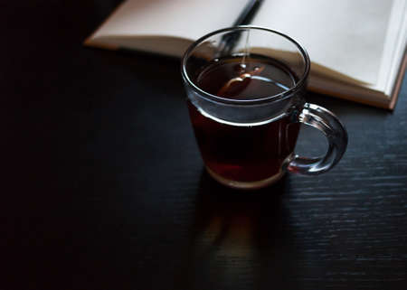 A notebook with blank pages, a black pen, glass mug with teabag on dark desk Stock Photo