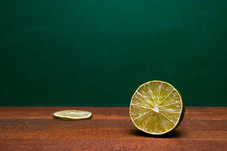 Cross Section Of A Lime And A Lime Slice On A Wooden Table. Green Background. Organic Accent To The Flavors Of Foods And Beverages.
