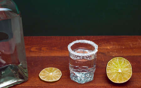 Alcohol Silver Tequila Shot Rimmed With Salt On A Wooden Rustic Table. Cross Section Of A Lime, A Lime Slice And A Bottle. Green Background.