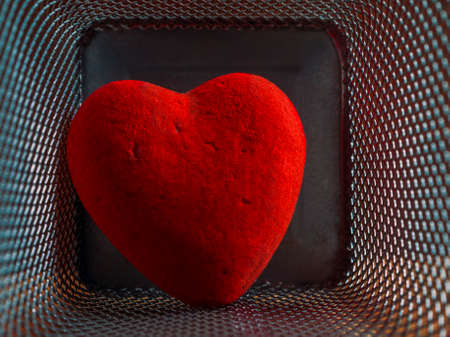 Red Wounded Velvet Heart in a Mesh Cage. Love, Home Violence, Loneliness, Freedom and Heartache Concept. Imagens