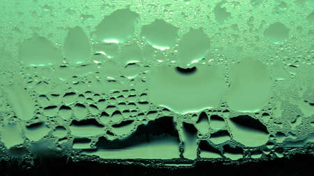 Condensation, Vapor, Rain, Water Drops Of Various Sizes On A Glass Surface.  Green Tone Color. Stock Photo