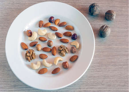 Mix of Almonds, Hazelnuts, Walnuts, Cashew Nuts on a White Plate, and Three Whole Walnuts on Light Wooden Table Surface. Healthy Organic Snack, Breakfast, Food Ingredients. Top View.