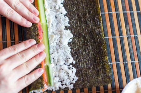 Making Sushi Rolls at Home: Female Hands Roll Nori Seaweed Sheet on a Bamboo Mat.  Ingredients: Salmon Fish Strips, Cucumber Sticks, Cream Cheese and Rice. Top View