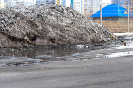 Big Pile of Dirty Melting Snow in a Parking Lot with Puddles and trash Collected over Winter Time. Warm Spring Day