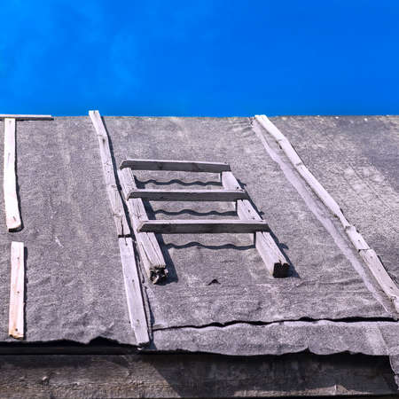 Section of a Wooden Ladder on a Barn Roof Covered with Waterproofing Tar Paper Against Summer Blue Sky. Roofing Repairs, Construction Concept