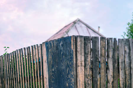 Old Rustic Wooden Board Fence with the Roof of a House and Garden behind At Sunset