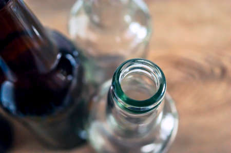 Top-Down View of Glass Bottle Rim, Bore, Orifice or Throat. Blurred Empty Glass Bottles, Wooden Background. Healthy Living and Detox Concept. Abstinence, Alcoholism Treatment.