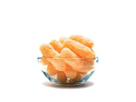 Yellow Corn Puffs in a Glass Bowl Isolated On White Background. Crunchy Flavored Puffed Snacks. Party, Movie, TV, Game Snacks.