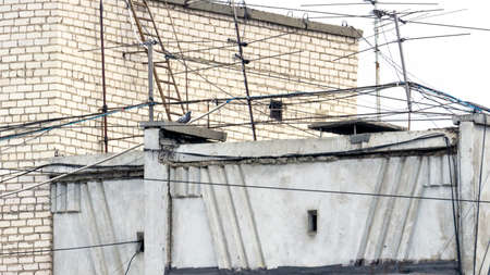 Web of Cable Wire Lines, TV Antennas on the Rooftop of a Building. Concrete Slabs, Brickwork