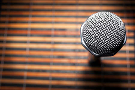 Top-Down View of A Microphone Head and Silver Grille on A Striped Yellow and Black Bamboo Mat Background. Karaoke Bar, Party Concept. Copy Space. Stock Photo