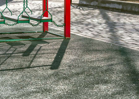 Outdoor Kids Playground Area, Paved Walkway in the Park on a Spring Afternoon with Long Shadows.