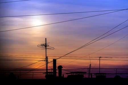 Dramatic Golden Sunset over Cityscape with Cable Wires and TV Antennas.