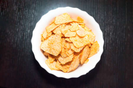 Top-Down View of a White Bowl of Ridged Potato Chips on Dark Wooden Background.