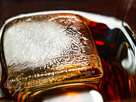 Big Ice Cube in a Glass of Whiskey and Coke Drink. Ice Texture Details 스톡 콘텐츠