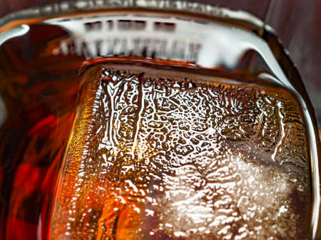 Big Ice Cube in a Glass of Whiskey and Coke Drink. Ice Texture Details Stock Photo