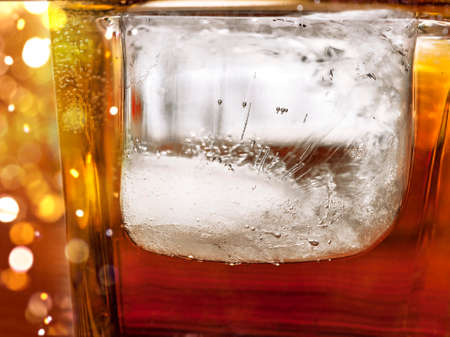 Big Ice Cube in a Glass of Whiskey and Coke Drink. Ice Texture Details. Celebration Lights. Stock Photo