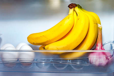 A Hand of Bananas, Four White Eggs and a Garlic Head in Open Refrigerator Door Plastic Container. Weight Loss Diet, Healthy Organic Food and Lifestyle Concept.