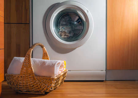 Wicker Basket with Clean Towels on the Floor by the Washing Machine with Laundry. House Interior Laundry Room. Wood Interior Design. Stock Photo