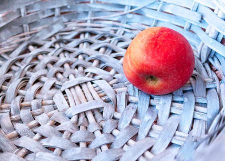 Single Red Apple in a Gray Wicker Basket. Copy Space. Stock Photo