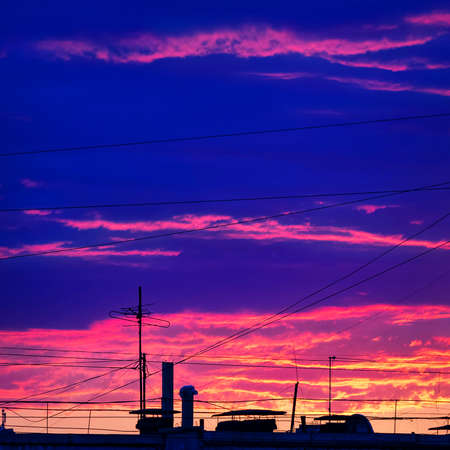 Colorful Sunset over the Urban Rooftop with Cable Wires and TV Antennas.