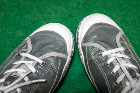 Pair of Dusty Gray Leather Gumshoes Sneakers with White Laces and Soles on Green Background. Top-Down View. Active People Concept.