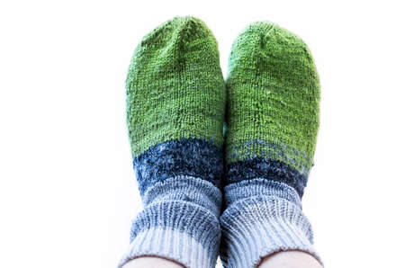 Feet In Green And Gray Handmade Knitted Woollen Socks on White Background. Keeping Yourself Warm Concept. Stock Photo