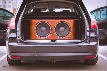 Rear View of a Car, Trunk and Front Doors Opened, With Installed Car Audio System, Sound Speakers and Subwoofer Sound Speakers in a Wooden Box.