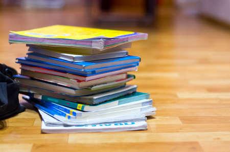 Pila de libros de texto y mochila negra sobre suelo de madera. Educación, vacaciones escolares, concepto de regreso a la escuela. Copie el espacio. Foto de archivo