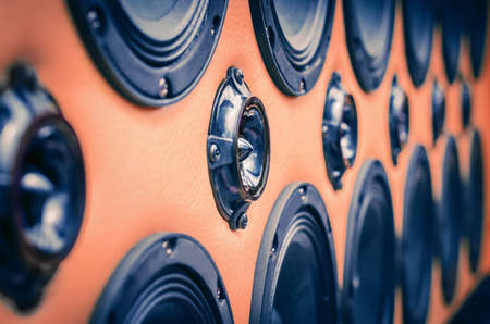 Perspective View of Rows of Sound Speakers on Light Warm Orange Background.