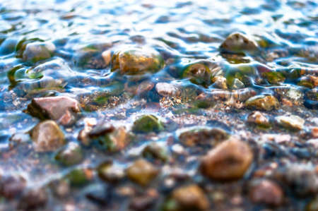 Close-up View of Colorful Pebbles in Water Waves. Travel Concept. Stockfoto