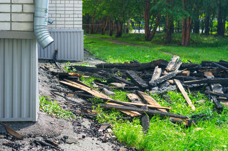 The Black Charred Rafters, Roof Framework, Nails Sticking Out, Debris on the Lawn near the Apartment Building with Downspout After the Fire. Insurance Concept. Stock Photo