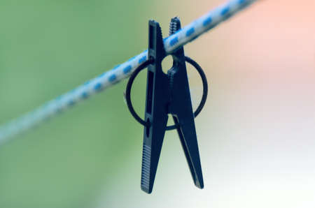 Black Plastic Clothespin on White and Blue Clothes Line On Blurred Background. Stockfoto