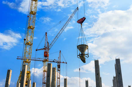 Crane Concrete Bucket, Yellow and Red Cranes, Vertical Reinforced Concrete Columns with Rebars at Construction Site.