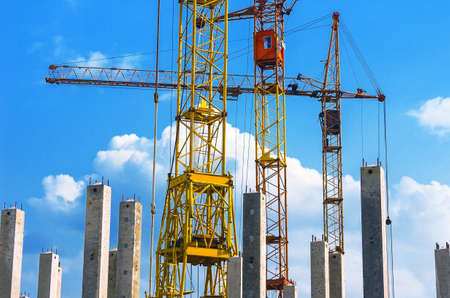 Yellow and Red Cranes, Vertical Reinforced Concrete Columns with Rebars against Blue Sky and White Clouds.