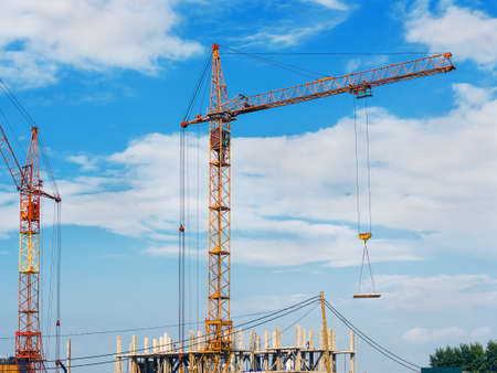 New High-Rise Building Construction Site with Yellow and Red Cranes against Blue Sky and Clouds. Stockfoto
