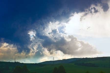 Dramatic Summer Thunderstorm Clouds Over Green Hills, Trees, Power Lines Stockfoto