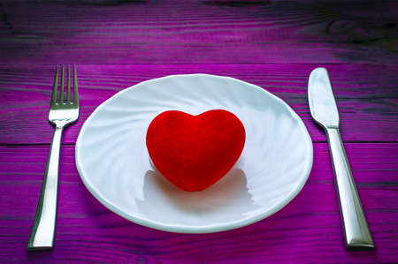 Red Plush Heart on a White Plate, Metal Fork and Knife on Dark Purple Wooden Table. Stockfoto