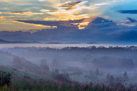 Dramatic Sunrise with Early Morning Mist over Forested Valley at Altai Mountains, Kazakhstan.