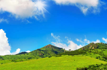 Summer Day with Blue Sky, White Clouds, Sunbeams over Green Mountains with Outcrops. Stock fotó