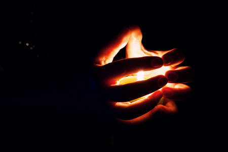 Female Hands around Burning Candle in the Dark.