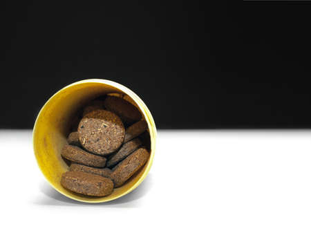 Herbal Supplement Pills in a Yellow Plastic Container on Black and White Background. 写真素材