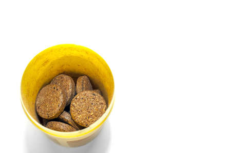 Top-Down View of Herbal Supplement Pills in a Yellow Plastic Container on White Background.