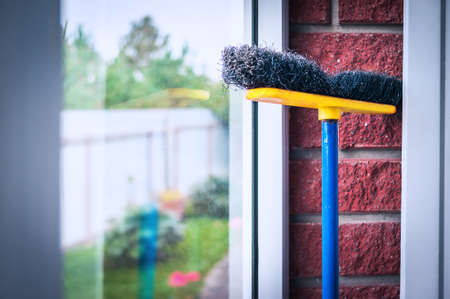 Yellow, Blue and Black Poly Push Broom Leaned Against the Glass and Red Brick Wall in the Mud Room. Keep Your Environment Clean and Tidy Concept.