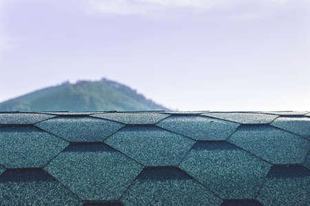 Rooftop of Green designer hexagonal asphalt, bitumen shingles on blurred background of a mounain peak and morning sky.