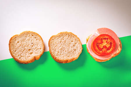 Two Slices of Fresh Bread with Sesame Seeds in Crust, One Open Sandwich with Slices of Cheese, Cooked Sausage and Tomato on Top. Angled Green and White Background.