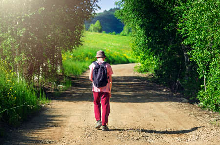 A Tired Guy in a Pink T-Shirt, Red Pants, and Bucket Hat, with Black Backpack and Long Pole Walks along Highland Country Road with Grassy Hillside and Birch Trees along the Road on a Hot Summer Day. Imagens