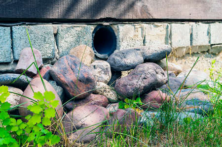 Plastic Pipe Vent in a House Foundation to Ensure Air Circulation under the Floor and to Prevent Mildew and Rot. Colorful Boulders on Mowed Grass. Reklamní fotografie