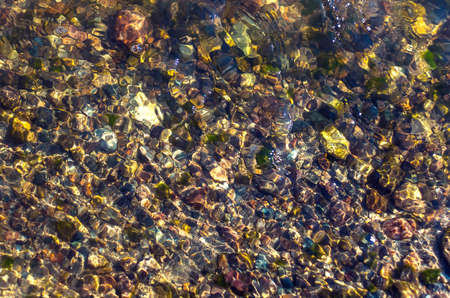Colorful Pebbles in Glittering Water Ripples. Organic Natural Background.