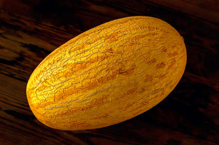 Fresh yellow melon on dark wooden background