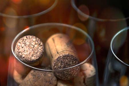 Catering, concetto di festa: immagine ravvicinata di un bicchiere di vino con tappi di sughero e bicchieri vuoti su uno sfondo di legno scuro. Messa a fuoco selettiva.